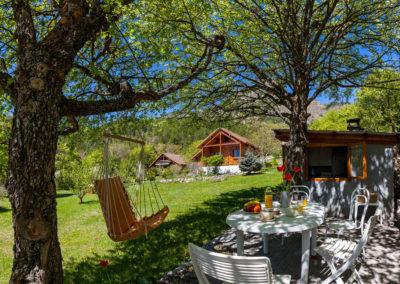 Le Chalet Carpe Diem, son jardin, sa terrasse ombragée et la cuisine d'été