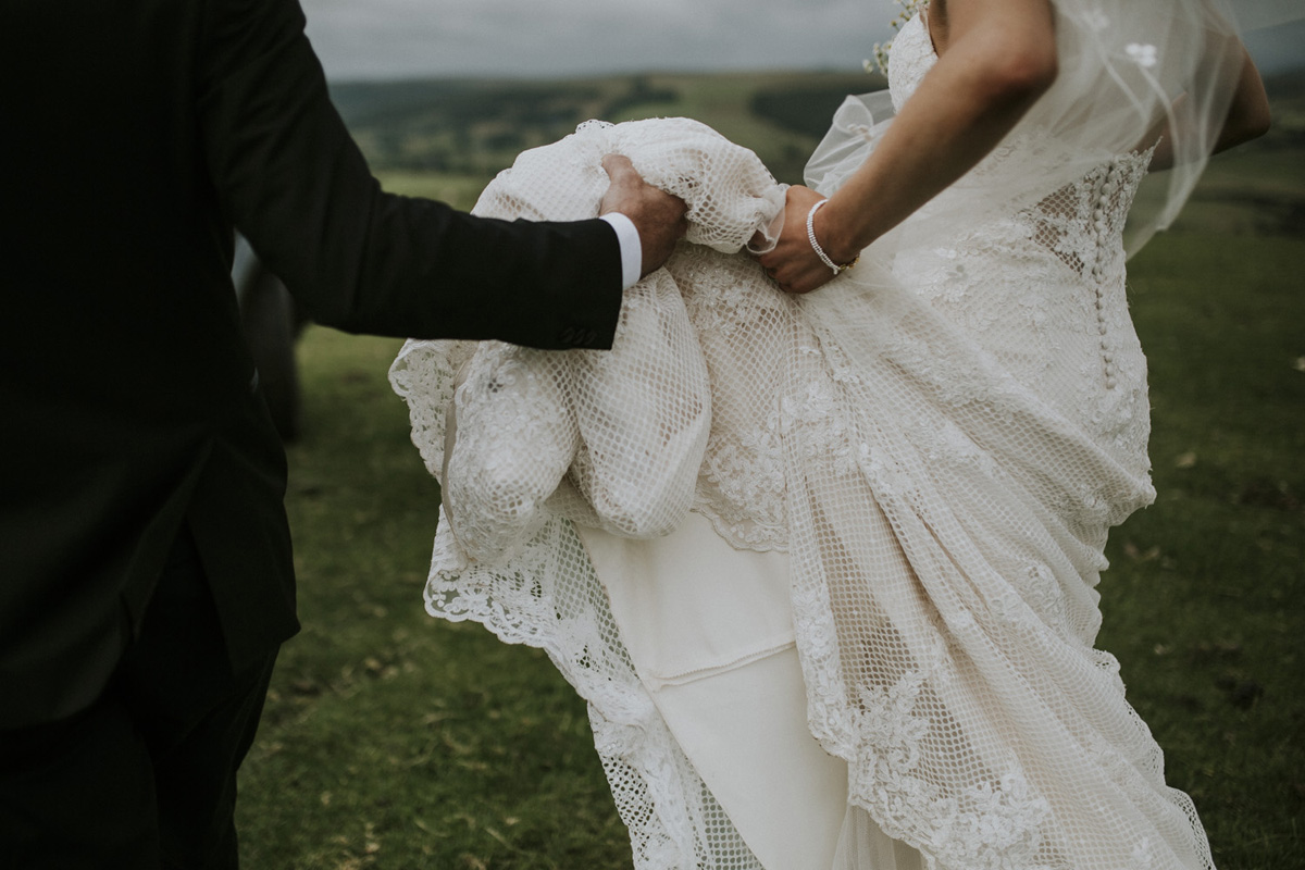 groom holding brides dress