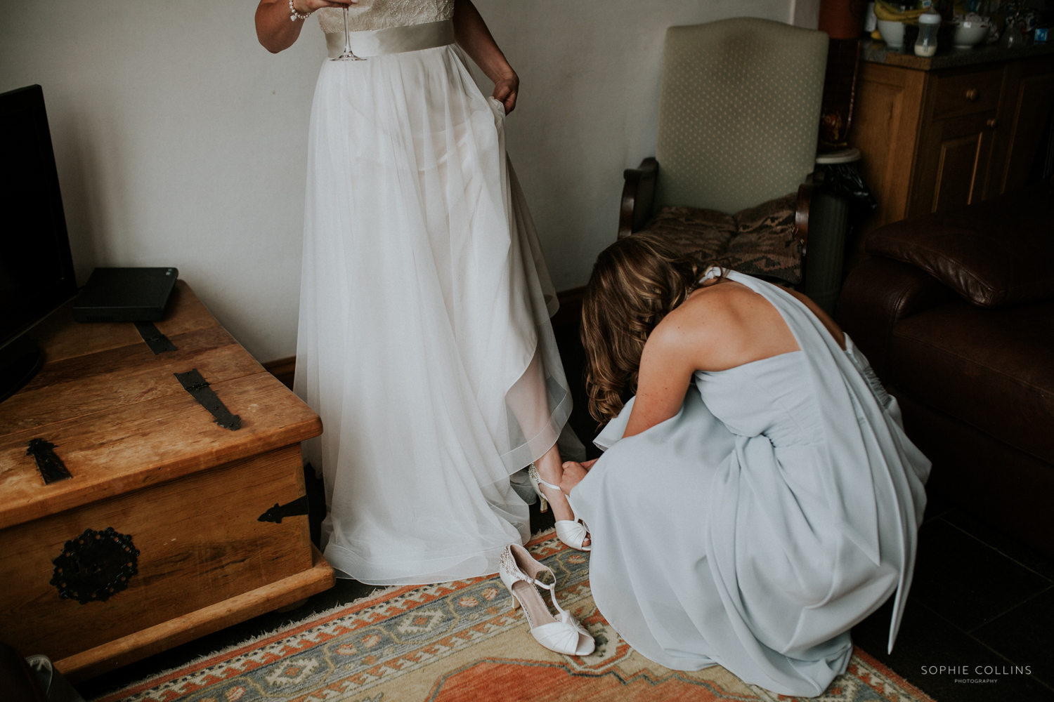 bridesmaid helping with brides shoes