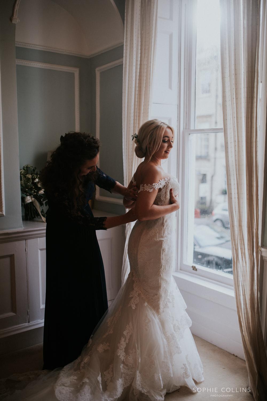 sister doing brides dress