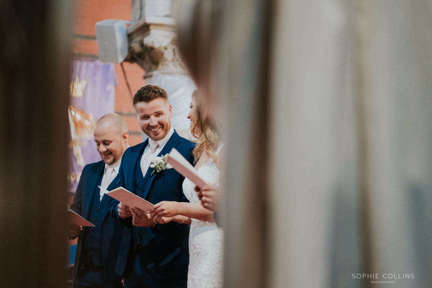 groom smiling at the bride in the church