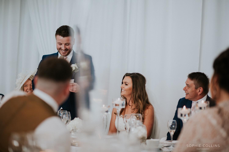 bride smiling, groom speech
