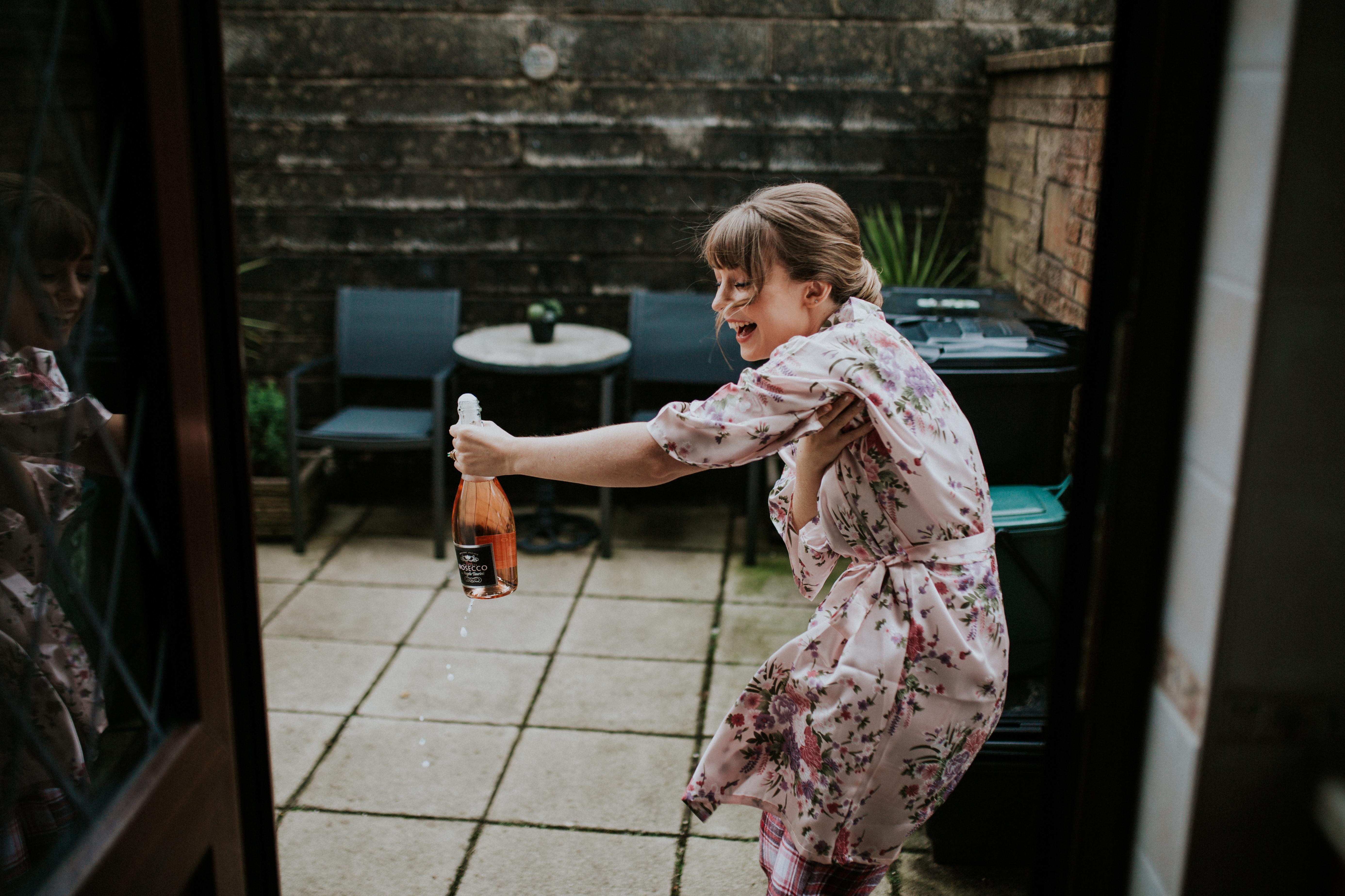 bridesmaid opening bottle