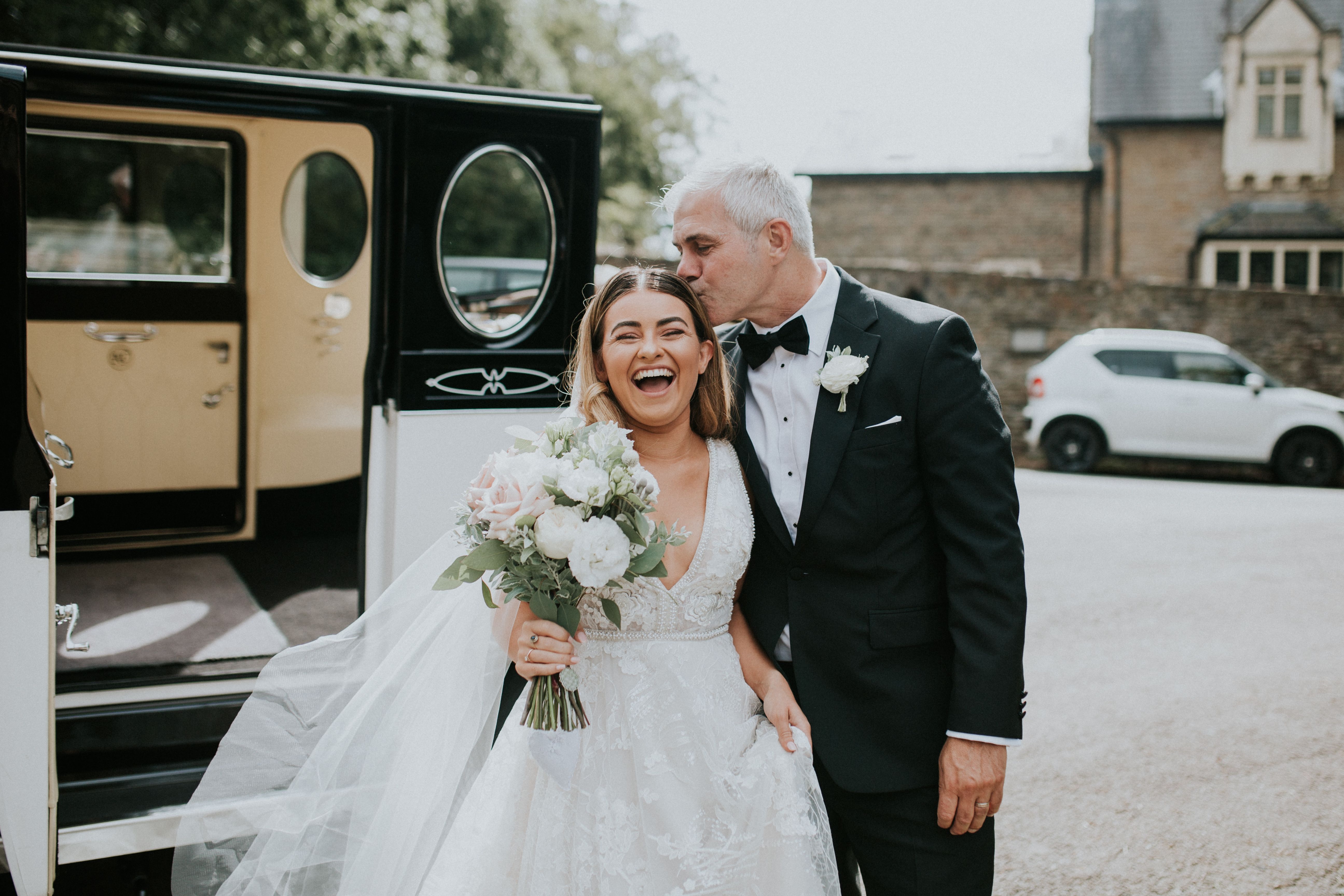 father of the bride kissing brides head