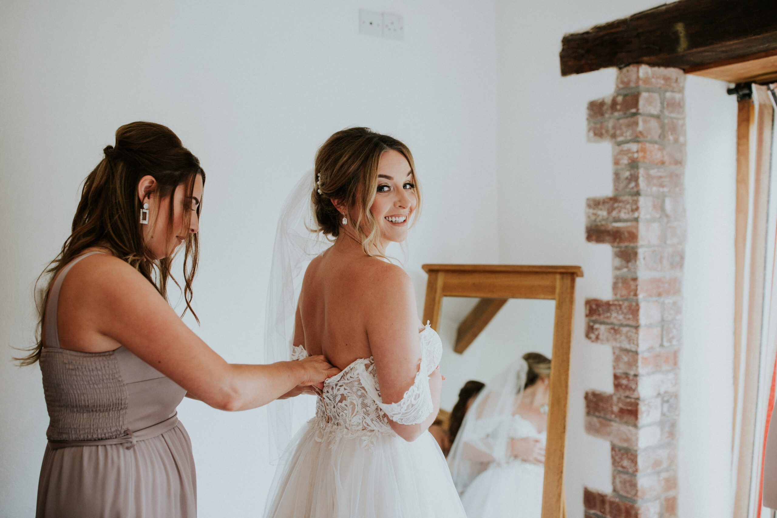 bridesmaids doing the back of the brides dress