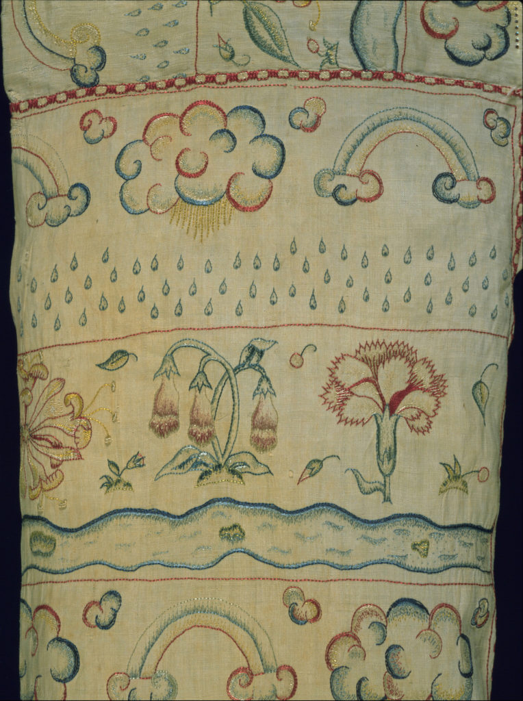 Title: Woman's smock Place:England Date: c. 1600 Medium & technique: Linen, hand-embroidered with coloured silks Dimensions: 40 x 1390 mm (bodice and sleeves) Themes: Bodies - Inside & Outside Collection: (c) the Whitworth, The University of Manchester The embroideries shown in this detail – featuring carnations, foxgloves and honeysuckle – decorate an early-seventeenth-century woman's smock, or shift. Originally full length, only the patterned bodice and sleeves have survived and it is likely that the owner cut off the plain, lower half of the garment after the linen became marked or damaged. One of the functions of an undergarment like this smock was to draw sweat and impurities away from the body and various contemporary authors mused on the consequences of wearing dirty or clean linens. From sweet-smelling flowers to a shower of raindrops and clouds anticipating a storm, the embroideries on the smock remind us of the influence of the environment on the body and the role of this garment in shielding the wearer from the hazards of bad air and excess heat or cold. Elizabeth Currie, Victoria and Albert Museum/ RCA