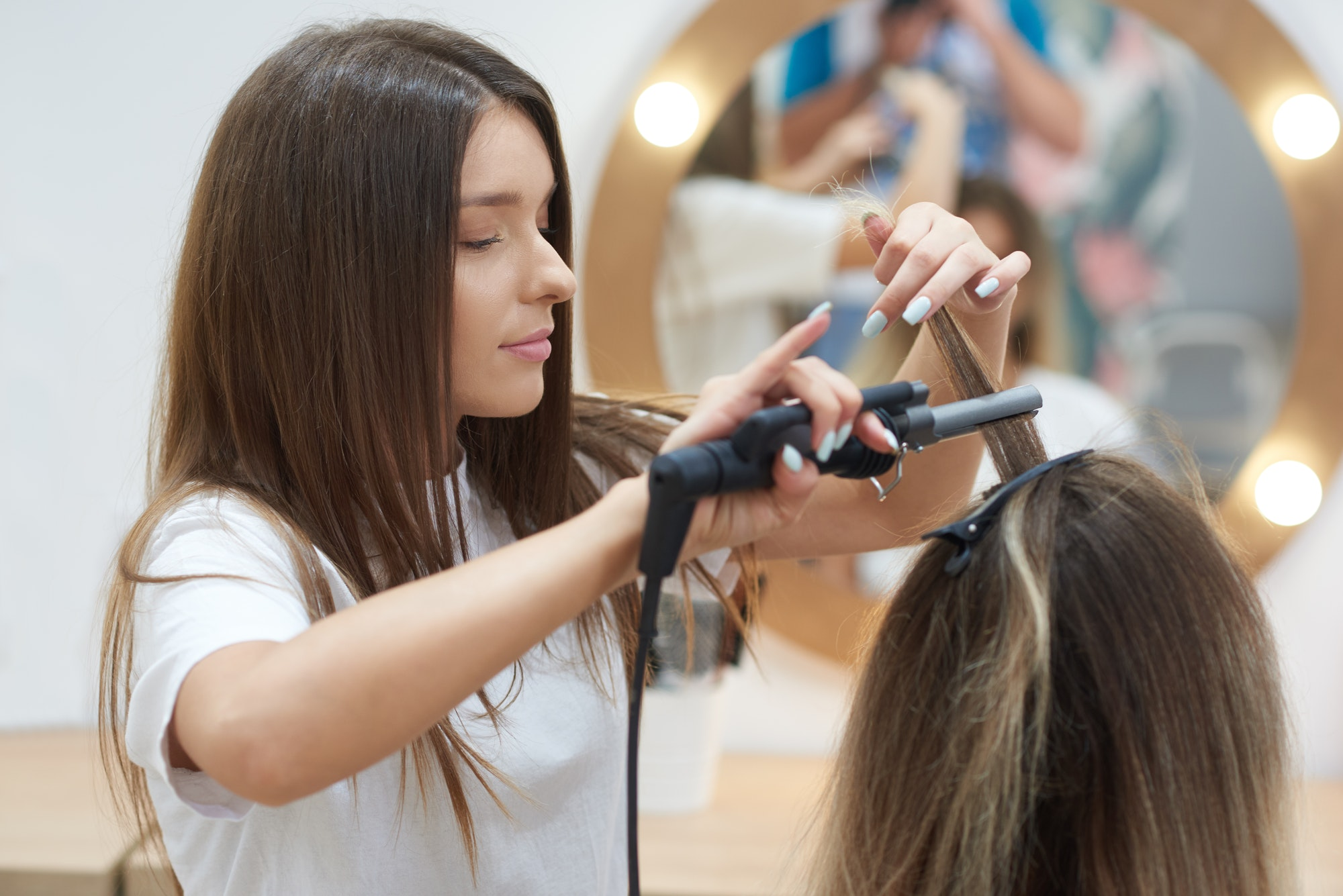 Side view of hairdresser in process of making styling for female in beauty salon