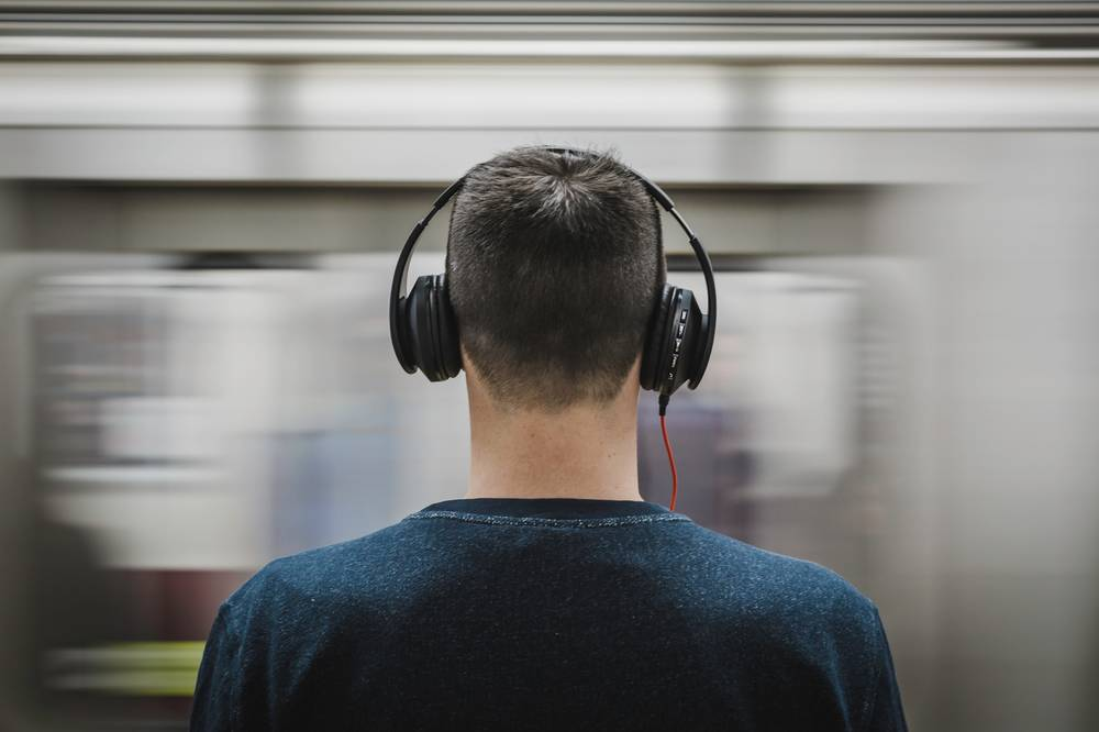 man headphone listening to add sugar podcast about ua finance and scaling up your game