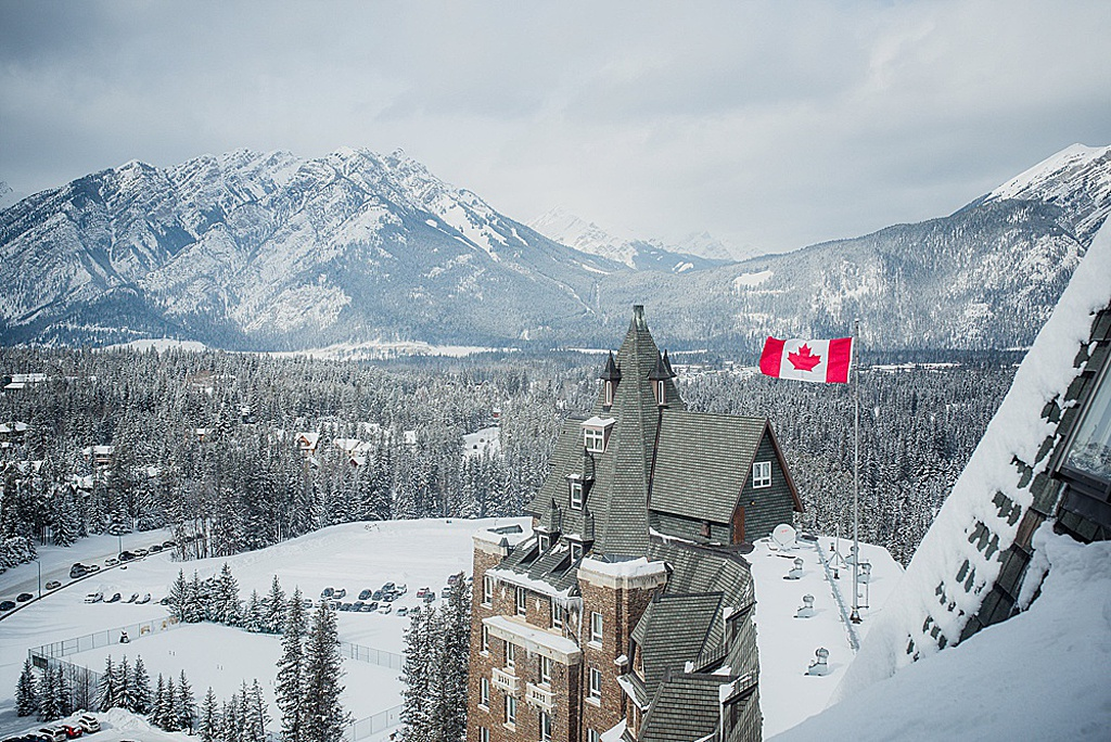canadian-flag-waving-atop-banff-springs-hotel-rockies-in-background