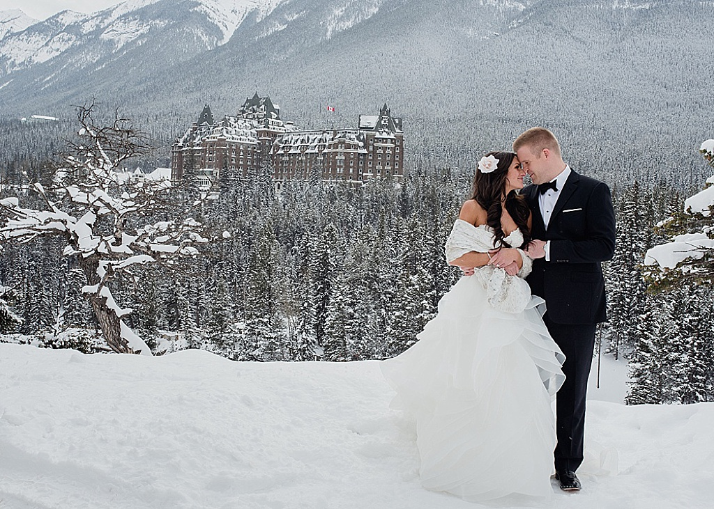 couple-standing-in-front-of-banff-springs-hotel-winter