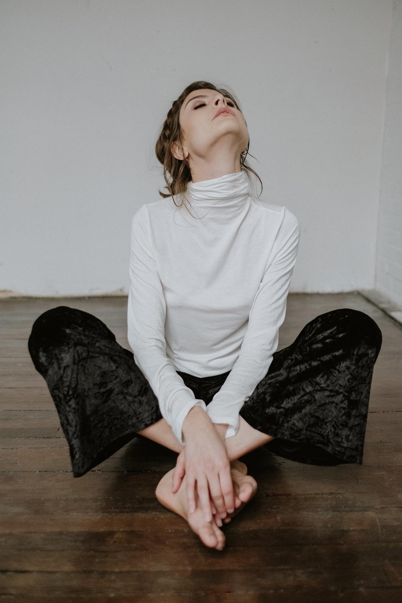 model-sitting-on-floor-cross-legged-looking-up