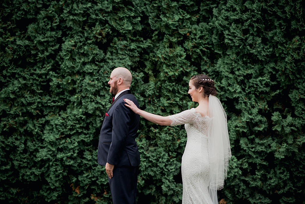 bride-groom-first-look-hand-reaching-out-to-shoulder