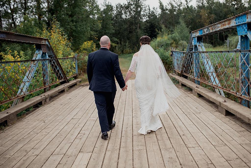 bride-groom-walking-away-on-bridge-holding-hands