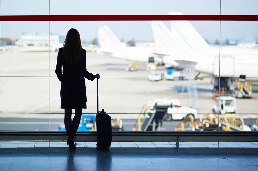 woman with suitcase looking at plane