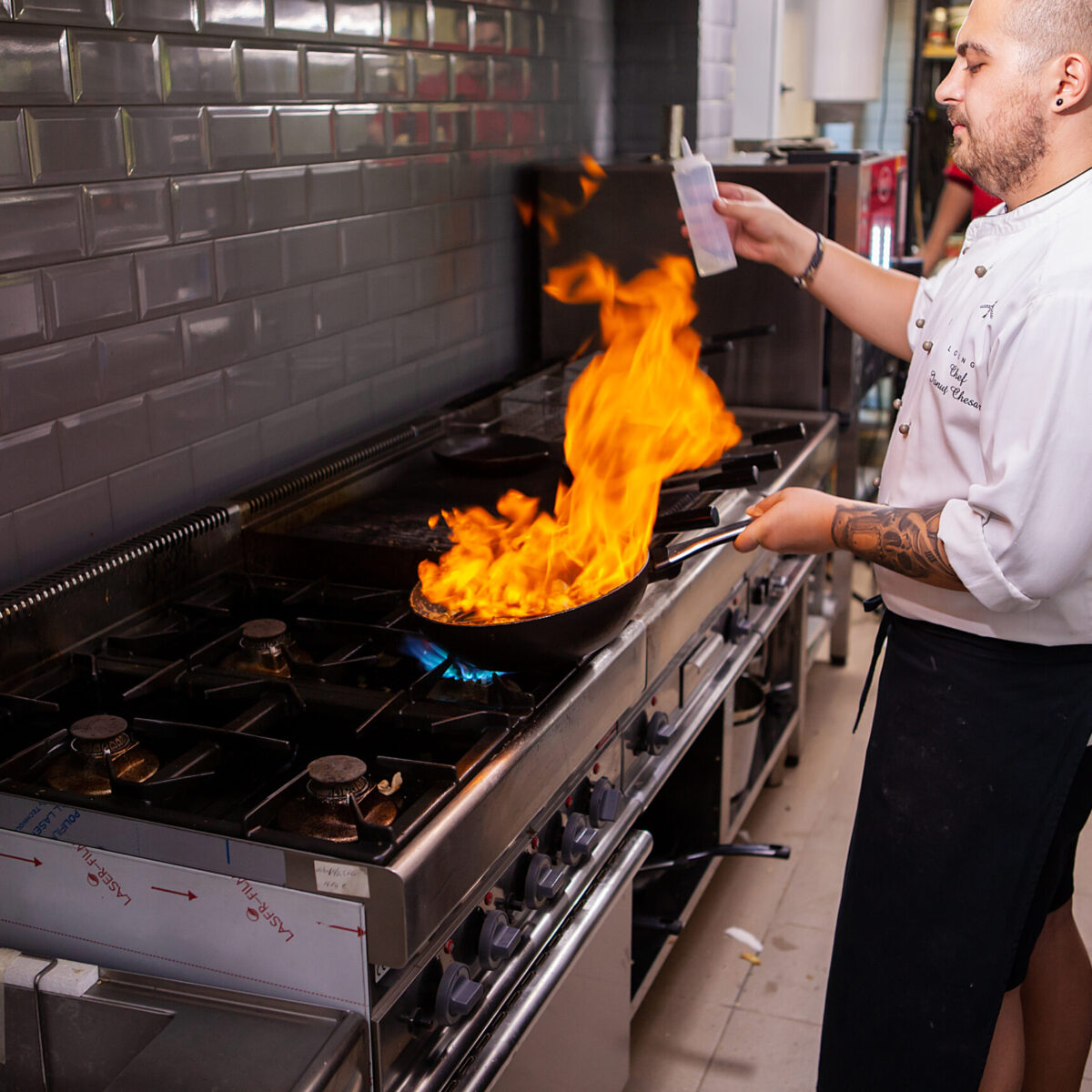 Male cook making flambe seafood at stove in restaurant kitchen. Tasty food
