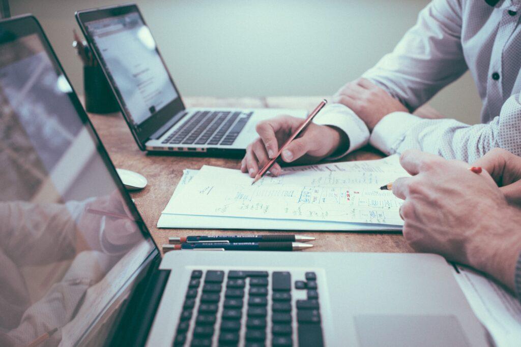 Zwei Geschäftspartner analysieren ein mögliches Immobilienprojekt. Sie zeichnen mögliche Projektpläne auf einem BLock Papier auf.