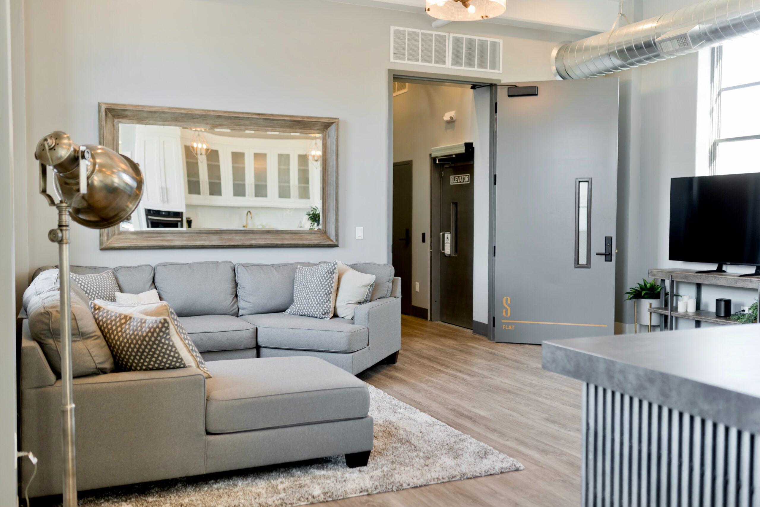 Eine Wohlfühloase mit grauem Sofa und flauschigem Teppich auf der linken Seite. Der Raum wird durch eine Lampe am linken Rand wunderbar erhellt. Auf der rechten Seite ist ein schönes Siteboard inklusive Fernseher zu sehen.