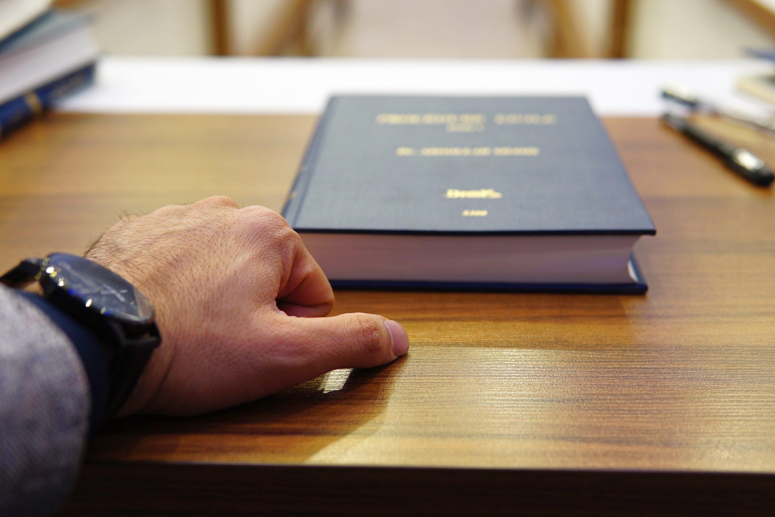 Ein hochdekorierter Immobilienanwalt legt bestimmt seine Hand auf den Tisch um seine Vertragskonditionen zu unterstreichen.