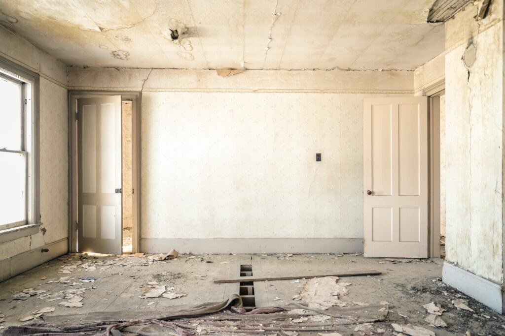Ein total verwüstetes und leeres Wohnzimmer mit Drang nach dem Zurückerlangen von Schönheit uns Stil. Die perfekte Ausgangslage für Immobilieninvestoren.