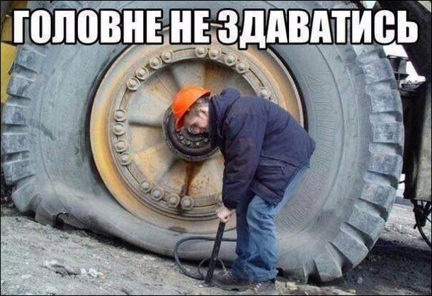 Головне не здаватись. Чоловік качає ручним насосом колесо від БелАЗа