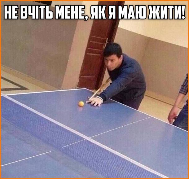 Не вчіть мене, як я маю жити! Хлопець грає в настільний теніс (пінг-понг) більярдним києм