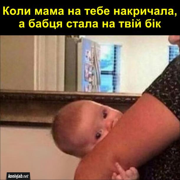 Смішне фото про малюка. Коли мама на тебе накричала, а бабця стала на твій бік. Немовля на руках в бабусі показує середнього пальця