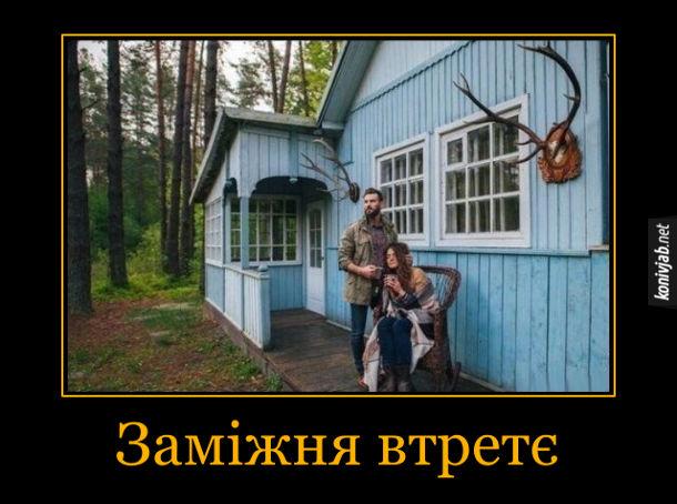 Демотиватор про подружню зраду. Дівчина заміжня втретє: Поряд з нею стоїть теперіщній чоловік, а на стіні висять роки двох попередніх чоловіків