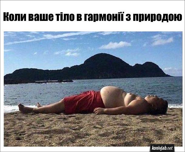 Смішне фото з пляжу. На березі моря лежить чоловік з чималим черевцем. На задньому плані видніється гора, яка за контурами схожа на цього чоловіка. Коли ваше тіло в гармонії з природою