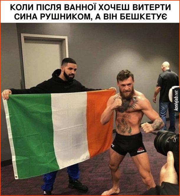Мем Мак-Грегор. Коли після ванної хочеш витерти сина рушником, а він бешкетує. Конор Мак-Грегор позує перед камерами, а позаду нього стоїть Дрейк і тримає ірландський прапор