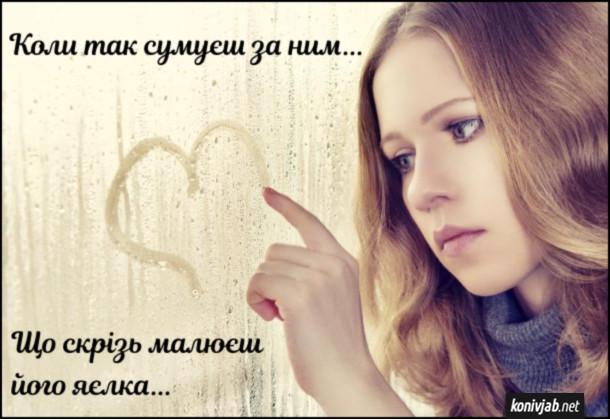 Мем про кохання. Коли так сумуєш за ним, що скрізь малюєш його яєлка... На фото дівчина малює сердечко на вікні