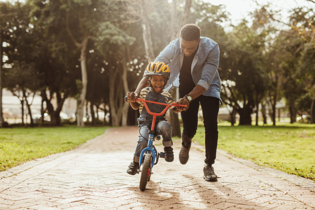 Boy,Learning,To,Ride,A,Bicycle,With,His,Father,In