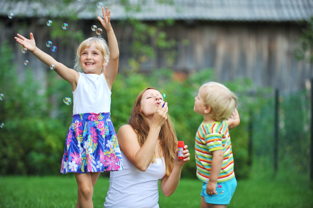 Mother,And,Her,Children,Play,With,Bubble,Blower,On,Green
