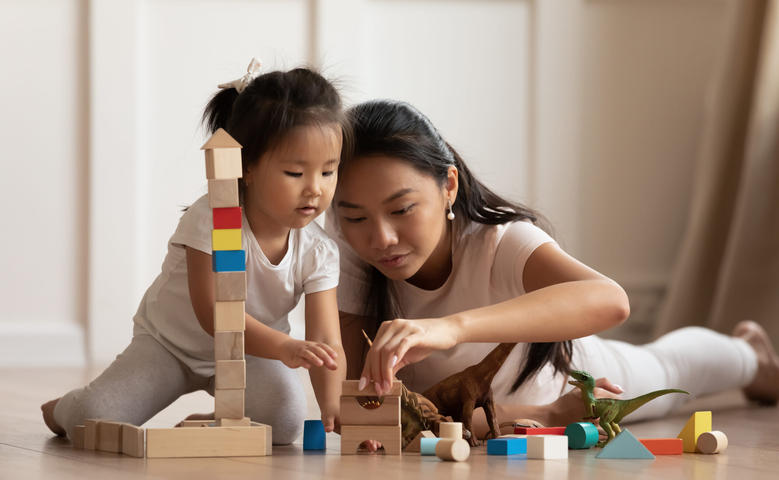 Involved,Little,Daughter,Her,Vietnamese,Mother,Play,On,Warm,Floor