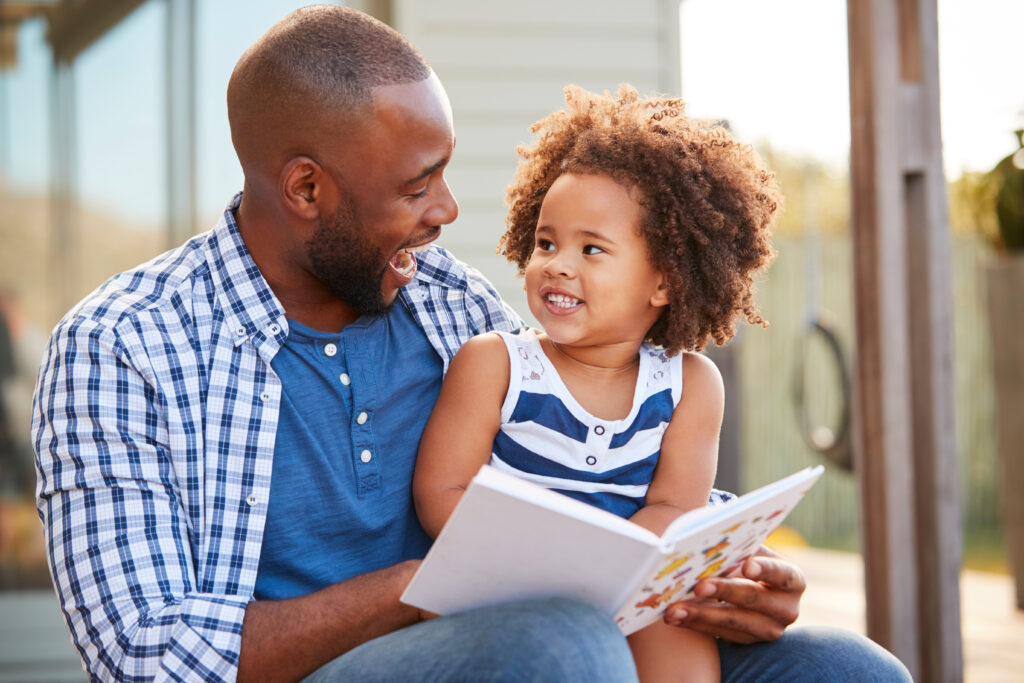 Young,Black,Father,And,Daughter,Reading,Book,Outside