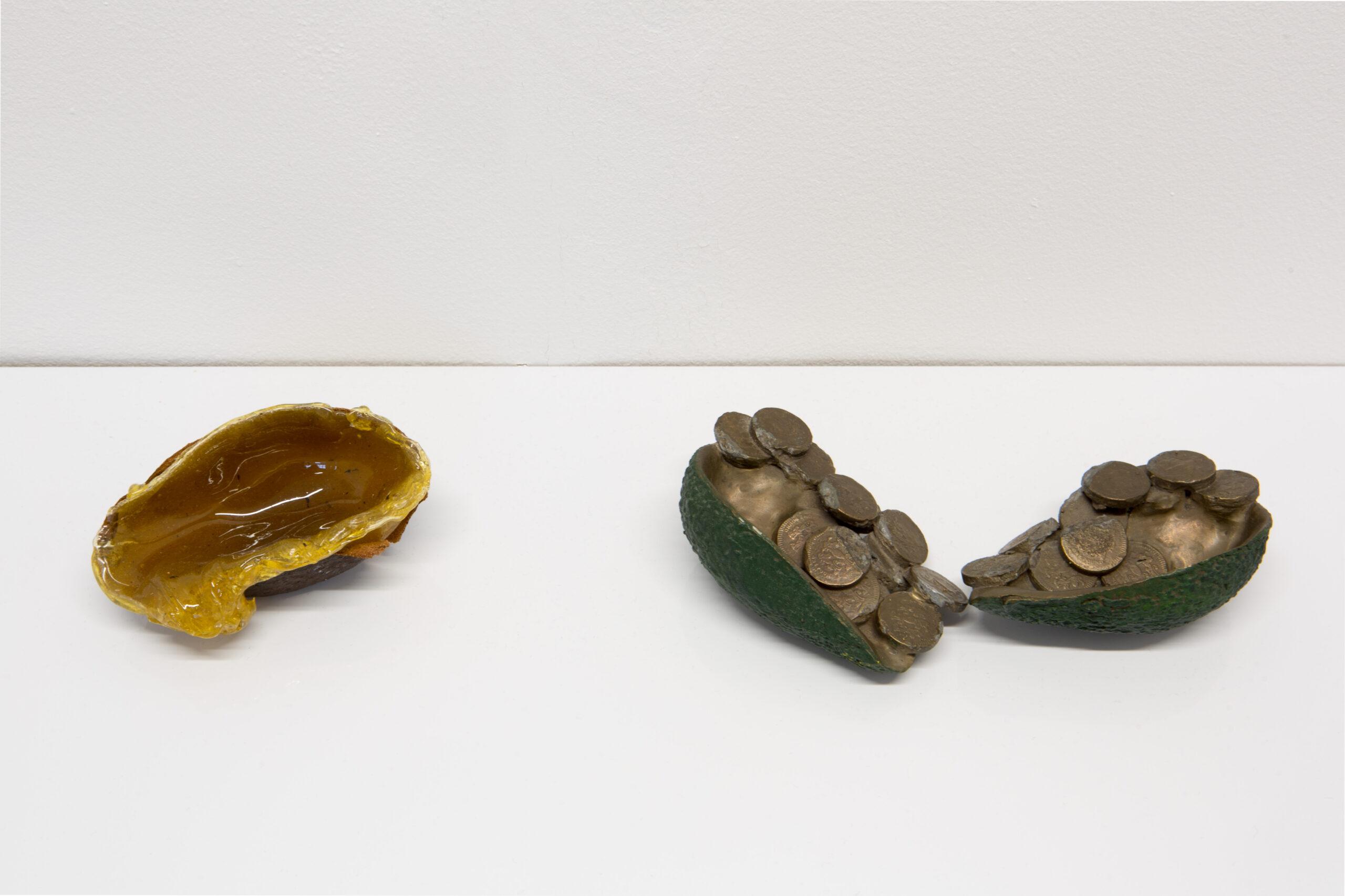 Lana Locke Avocado slime (2020) Glass wax and avocado skin, 5 cm x 11 cm x 6 cm. Lana Locke Avocado and coins (ii) (double) (2012) Bronze, 5 cm x 16 cm x 12 cm.
