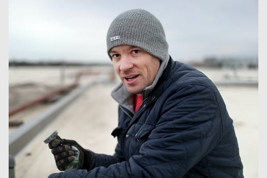 Scott Peterson holds a magnet up shilst sitting on the roof of a building