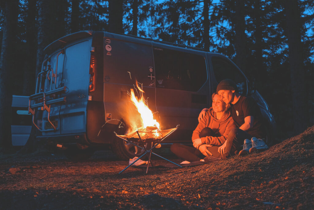 Stacey and Joel sat by the camp fire in Three Lochs Forest Drive at night