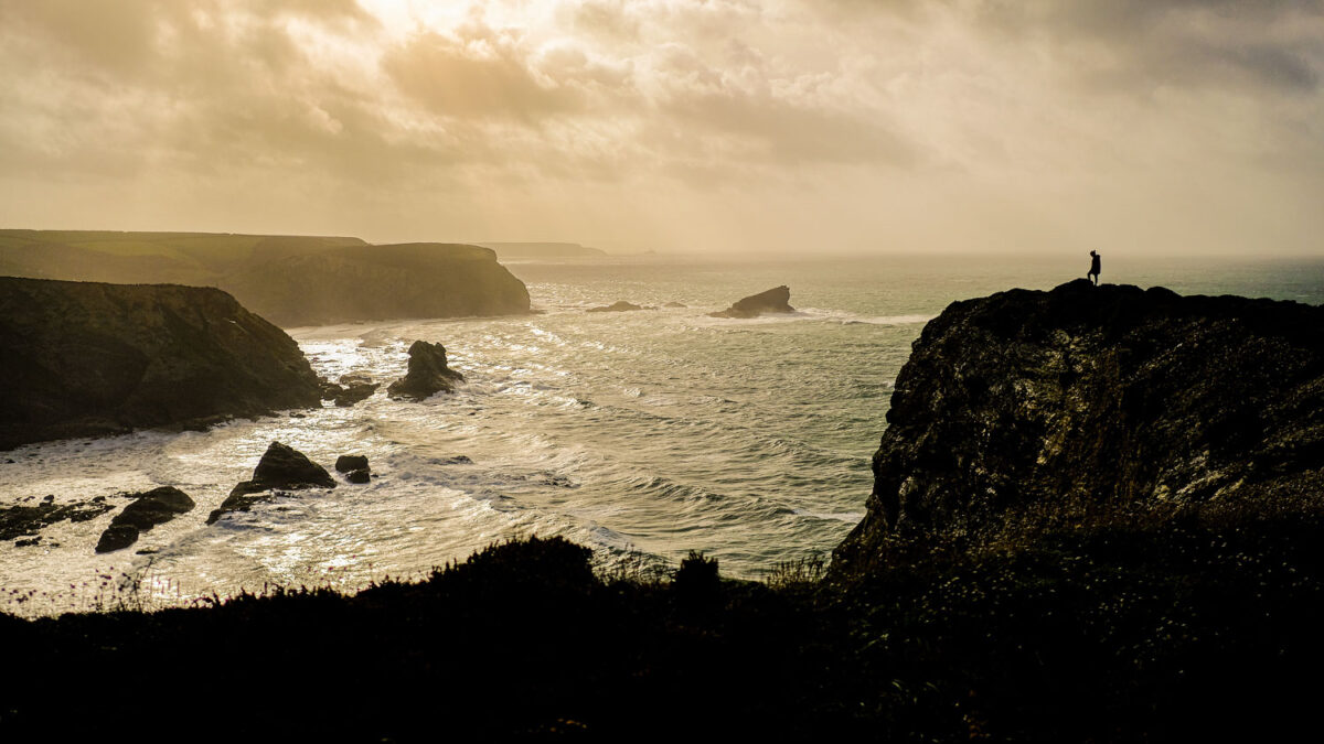 Stacey stood on a cliff edge near Portreatch, Cornwall, at sunset.
