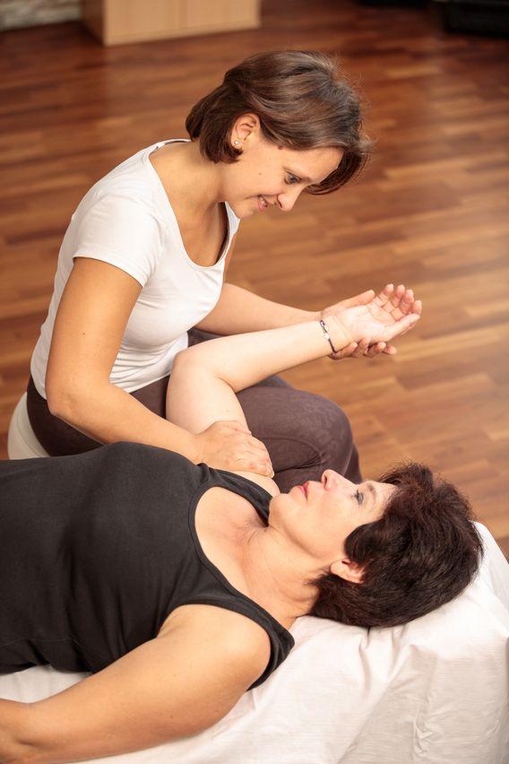 Liegende Frau wird mit Manualtherapie an der Schulter behandelt