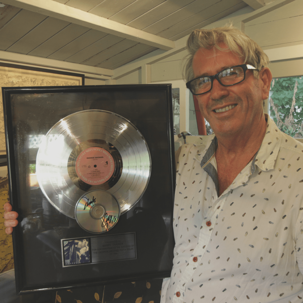 This is a picture of Garry Trainer standing with the disc he was presented with for participating in the George Michael 'Faith' Tour. Garry trainer is smiling while holding the disc close to his side.