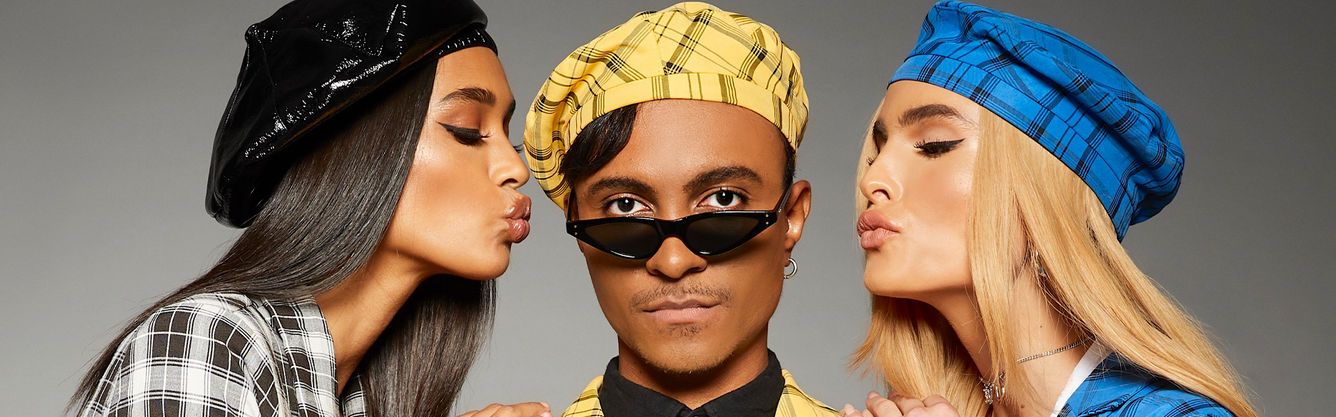 This is a picture of Hayden Williams (centre) with two Misguided models either sided of him giving him an air kiss on either cheek. Hayden is in yellow plaid and the two models are also in plaid, the one on the right is in blue plaid and the one n the right is in black and white plaid. All three in the picture are wearing a beret. Hayden is looking over the shades he is wearing, looking straight to camera.
