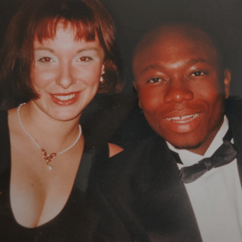 This is a picture of Ade at an Oxford University party. He is wearing a black tuxedo sitting next to a white lady who has red hair, red lipstick and a low cut black dress. Both are smiling cheekily and enjoying the party.