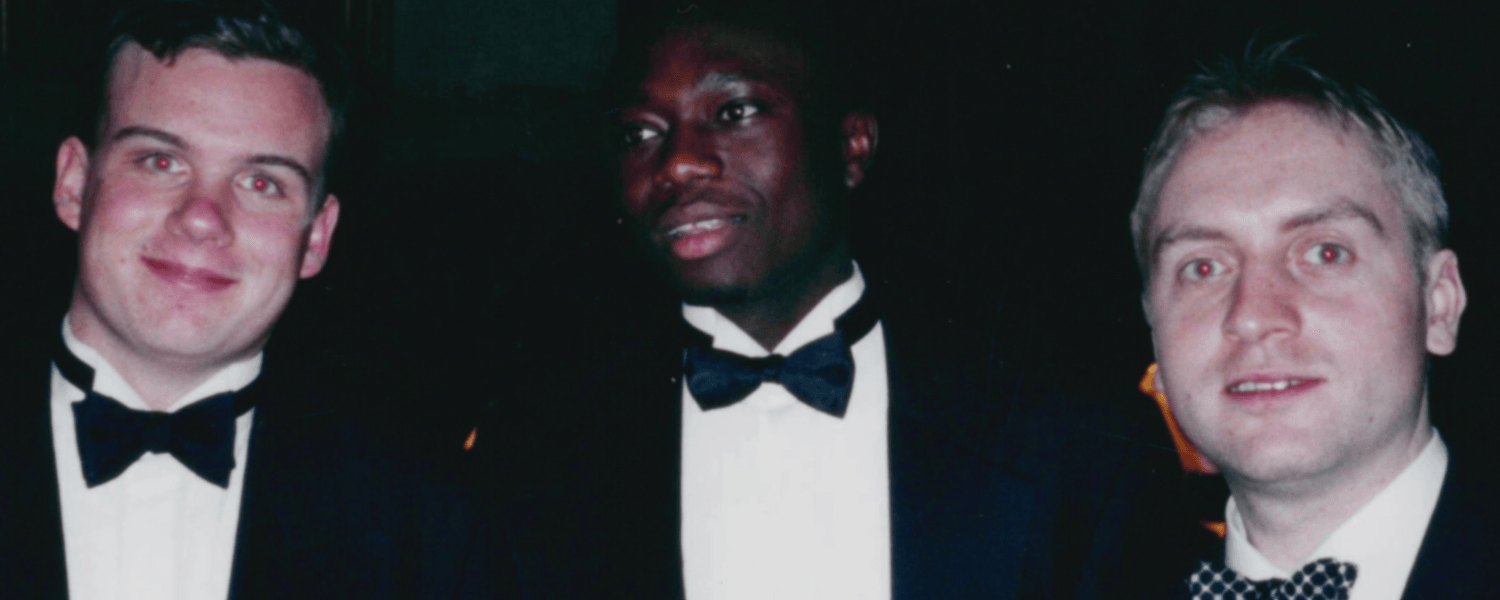 This is a picture of Ade and two University friends. All three are wearing black tuxedos. Ade is in the middle and his two friends stand either side of him looking to camera.