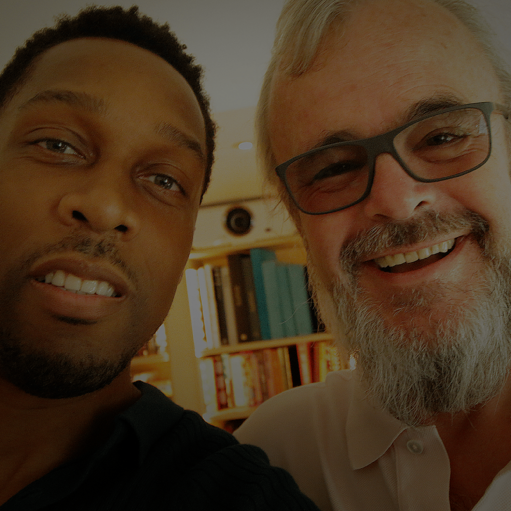 This is a picture of Richard Griffiths and Lemar. They are smiling towards camera. Richard wears a white shirt and has a white-ish beard. Lemar wears a dark top, the picture is a portrait selfie taken before their interview about the music industry, Lemar, Little Mix and Michael Jackson.