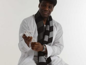 Angelo recalls playing for his brother while on campus at university. He sits on stool in this picture wearing white shirt and white trousers and a black and grey striped scarf.
