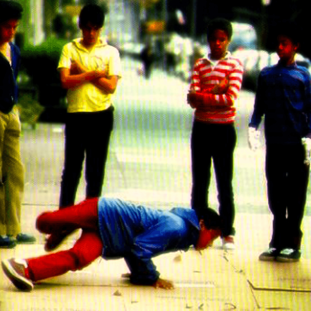 This is a picture of kids in the street break dancing. Four children stand while one prepares to do a breakdance move on the pavement.