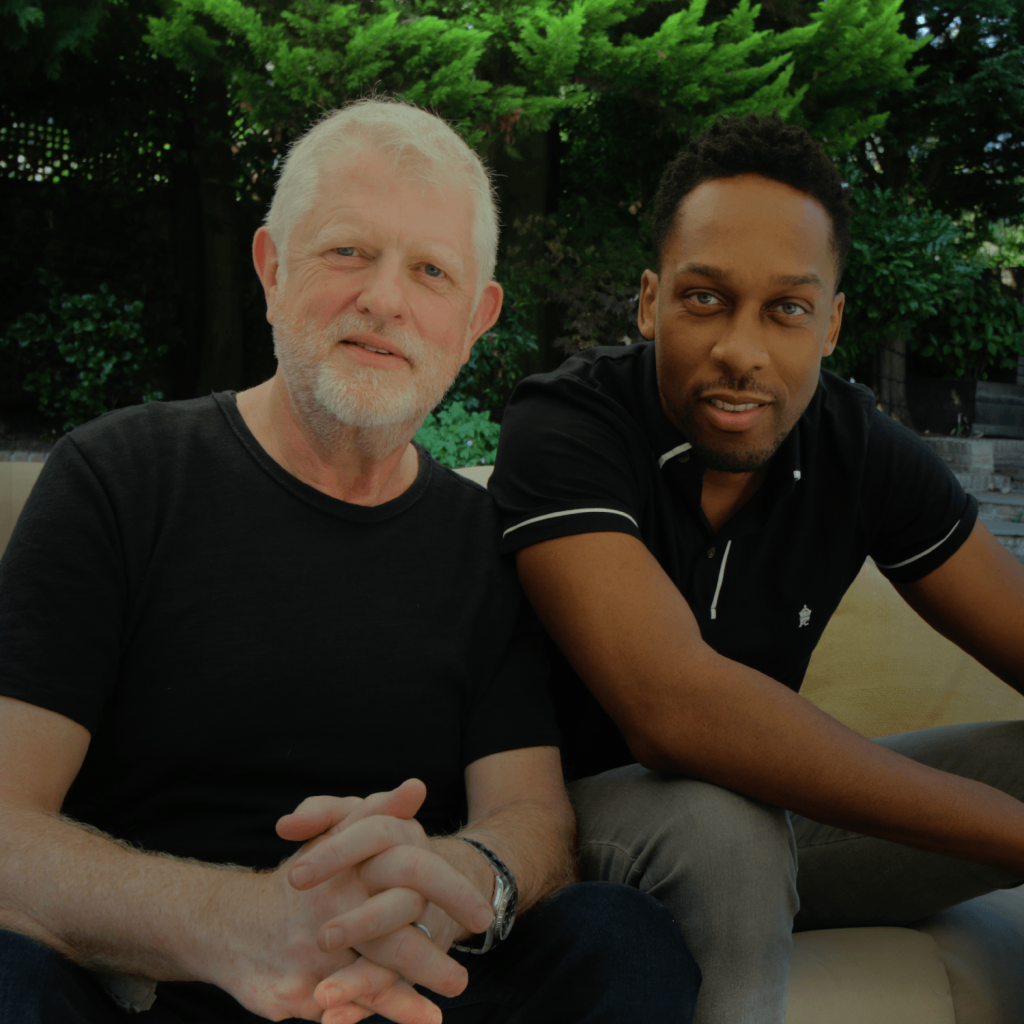 Harry and Lemar sit and face camera smiling before their talk on music, management, djing and Berlin hitchhikers. . Harry's hands are clasped and they are in a garden. Harry wears a black T shirt.