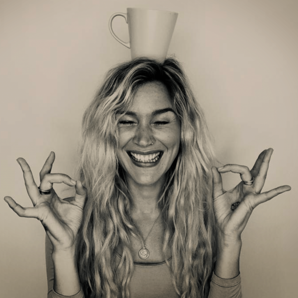 This is a black and white picture of Joss Stone balancing a white mug on top of her head for her podcast - A Cuppa Happy.