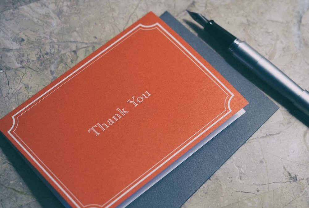 Thank you card laying next to a pen