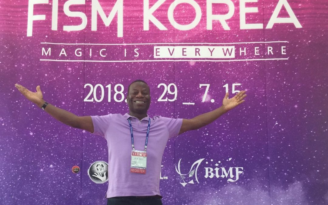 Craig Martin taking a photo in front of the FISM conference branded backdrop close up version